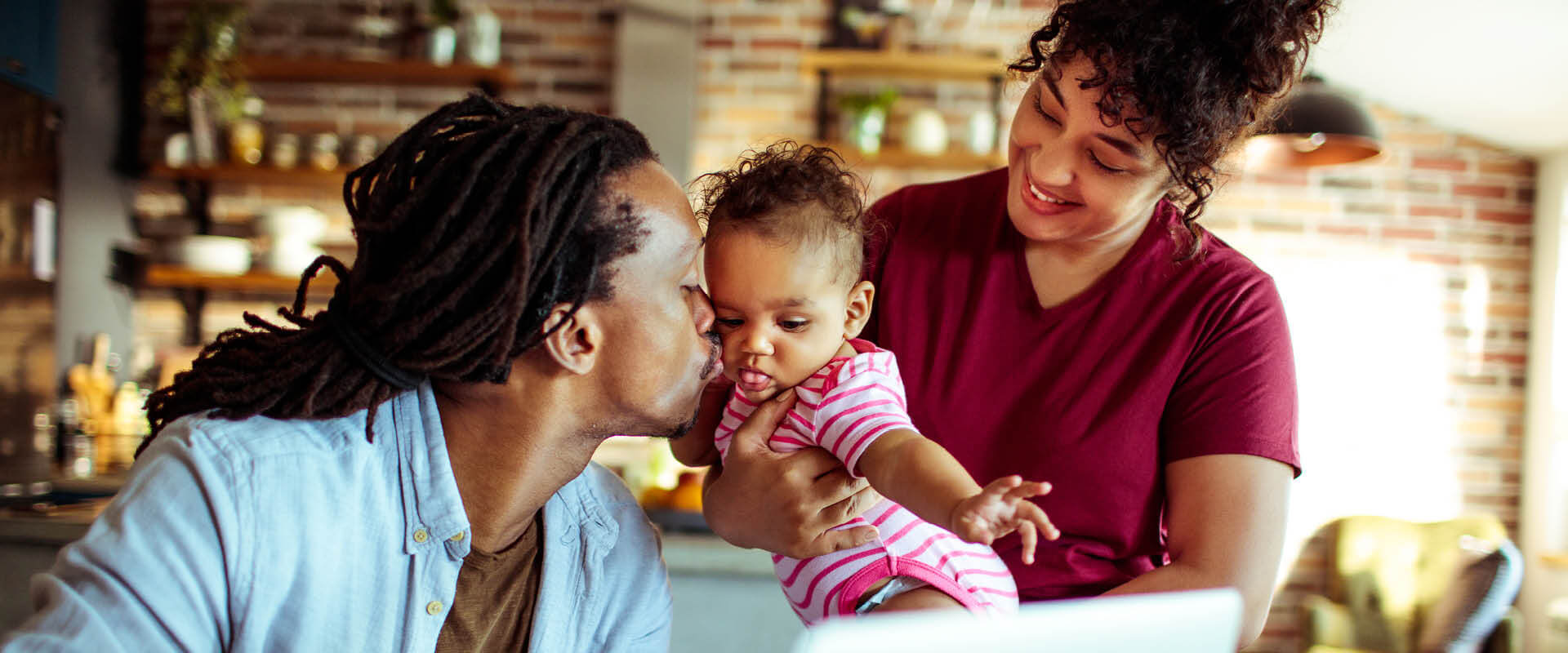 Diverse couple at home. Dad kisses daughter