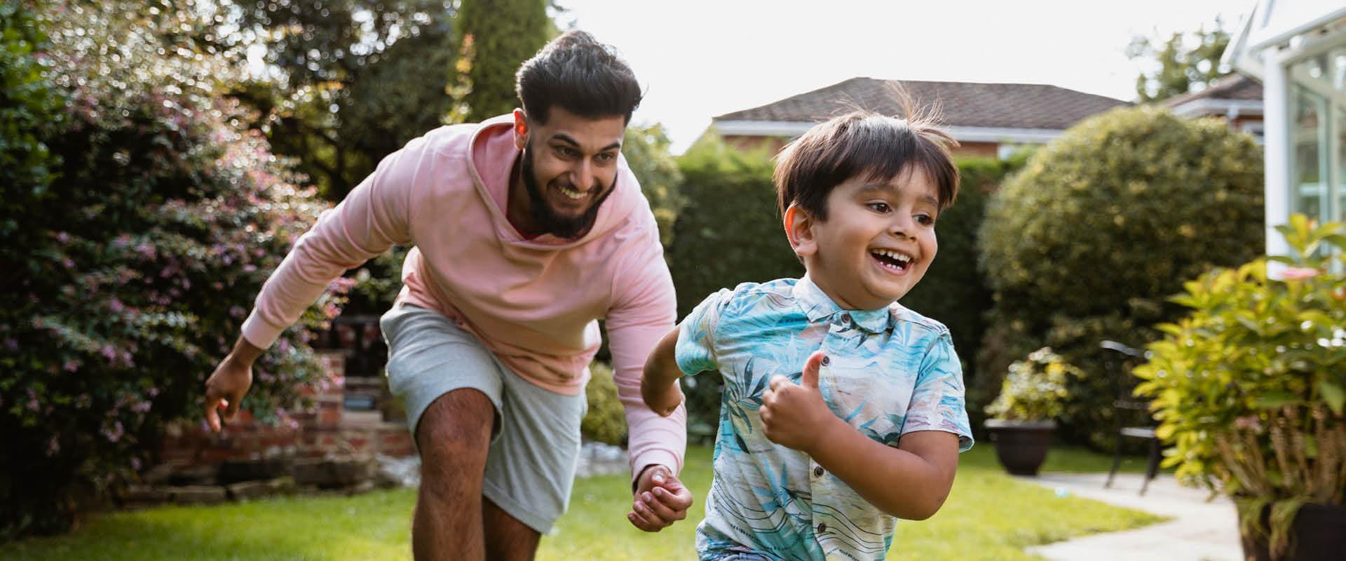 Father running after child in garden