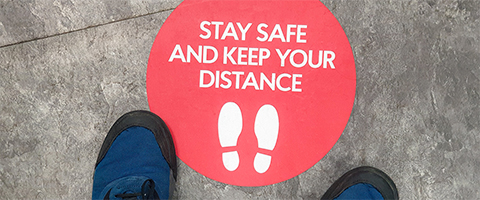 Keep your distance sign on floor
