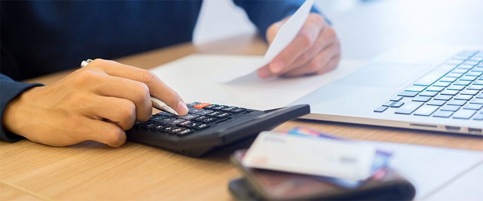 A person's hand and a calculator on a table