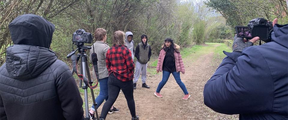 Junior filmmakers filming a scene outdoors